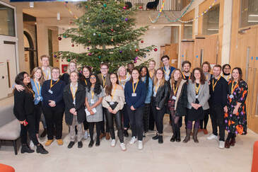 Group of students from the Student Teams posing in front of a big Christmas tree, indoors.